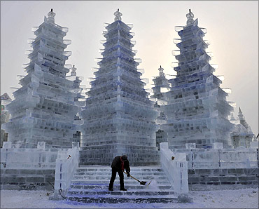 A worker cleans an ice sculpture of pagodas prior to the Harbin International Ice and Snow Festival