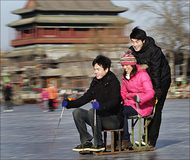 People ride a specially constructed 'ice-chair' on a frozen lake in front of Drum Tower in Beijing.