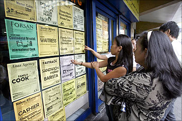 Applicants look at job offers displayed on a glass window of a recruitment agency in Manila.