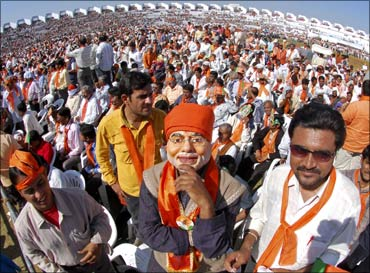 A Bharatiya Janata Party supporter wears a mask of Gujarat's Chief Minister Narendra Modi.