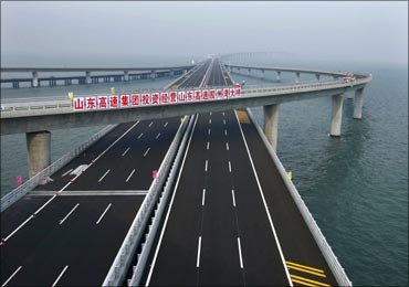 A sign that reads: 'Shandong Highway Corp. invests to operate Shandong Highway Jiaozhou Bay Bridge' is seen at Qingdao Jiaozhou Bay Bridge in Qingdao, Shandong province.
