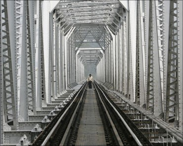 A man crosses a railway bridge on Teesta River near Siliguri