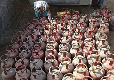 A vendor loads empty LPG cylinders.