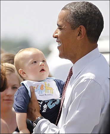 US President Barack Obama holds a baby during his visit to Fort Drum in New York.