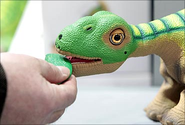 A man feeds a Pleo, an interactive robotic baby dinosaur toy, at the CeBIT computer fair in Hanover.
