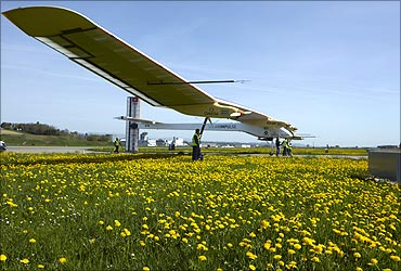 Staff push the Solar Impulse's solar-powered HB-SIA prototype airplane after a test flight.