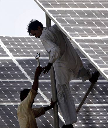 Technicians work on solar panel in power station at Hub about 25 km (15 miles) from Karachi.