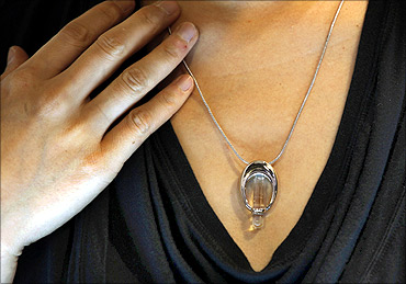 An exhibitor poses with a DNA necklace, a locket made by a Hong Kong co containing DNA of a person.