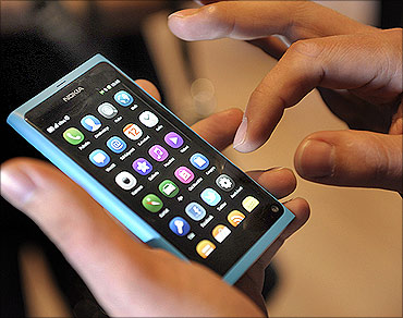 A staff member displays a Nokia N9 smartphone at a news conference in Espoo.