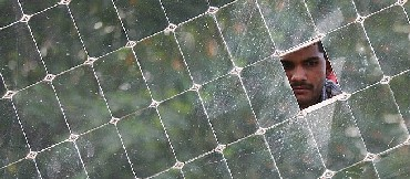 A worker looks through a solar panel at the Gadhia solar energy systems manufacturing unit at Gundla