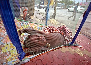 Five-month-old Rahul sleeps in a hammock next to shop along a sidewalk in Mumbai.