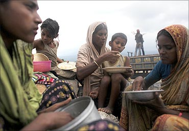 Stone worker Sajeda Begum eats lunch with her son Sohel during a break in work at Bholaganj.