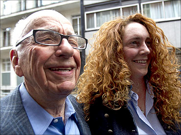 News Corporation CEO Rupert Murdoch leaves his flat with Rebekah Brooks, chief executive of News International, in central London.