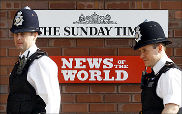 Police officers stand outside an entrance to News International  in London.