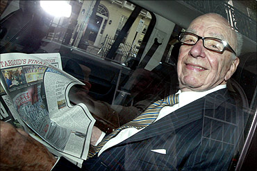 News Corporation CEO Rupert Murdoch holds a copy of The Sun as he is driven away