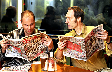 Men look at the last edition of The News of The World newspaper in the bar.