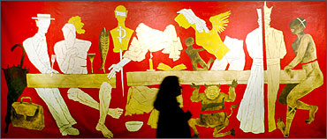 A visitor looks at a painting by M F Husain.