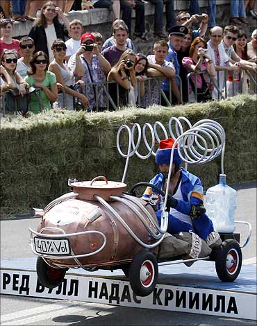 A participant in handmade cart in the form of a distillation apparatus takes part in Red Bull Rally.