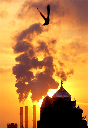 Smoke rises into the sky, as a cathedral is silhouetted against the sunset in St.Petersburg.