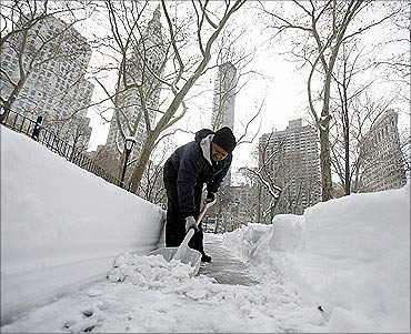 A worker shovels snow from the sidewalk in front of the New York Stock Exchange after a snow storm.