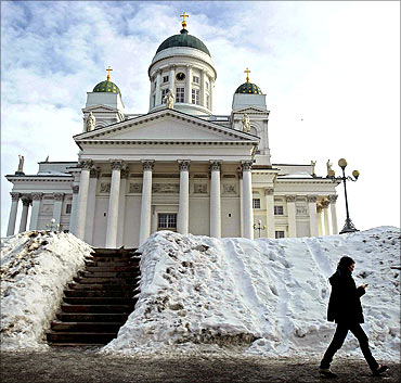 A woman walks past the Helsinki cathedral.