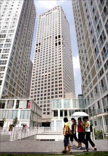 Women walk past buildings at Beijing's central business district.