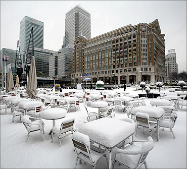Tables stand covered in snow in London's Canary Wharf.