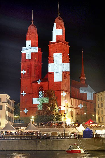 A light installation by Swiss artist Gerry Hofstetter illuminates the Grossmunster church in Zurich.