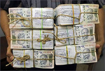 An employee carries bundles of currency notes.