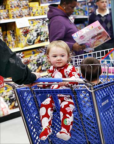 Anna Muller sits inside a shopping cart during Black Friday sales at the Toys R Us store in New York