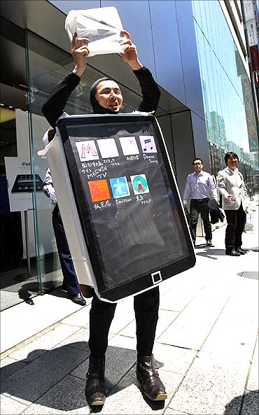 A man in a costume representing an iPad poses with his iPad in Tokyo.