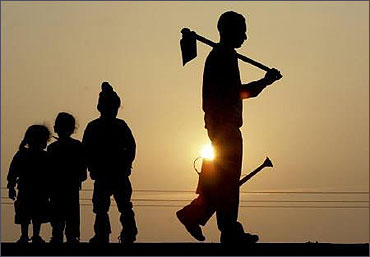 A labourer carrying his tools is silhouetted against the setting sun in Chandigarh.