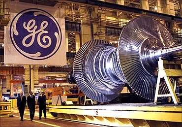 President Barack Obama (C) passes a turbine as he tours General Electric's birthplace in Schenectady