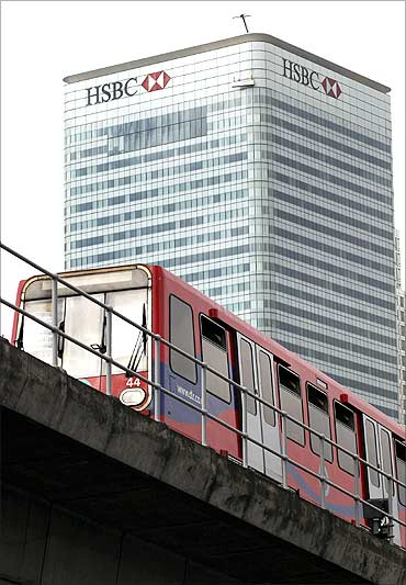 A commuter train passes the HSBC building on Canary Wharf in London.