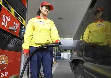A station attendant fills up a car at a PetroChina gas station in Beijing.