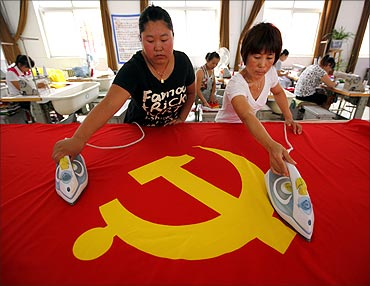 Workers use irons to smooth out a Communist Party of China flag at the Beijing Jingong Flag factory.