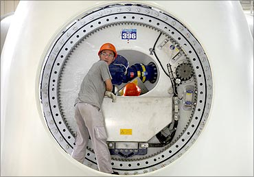A worker leans inside the shell of a wind turbine tower in the assembly workshop.