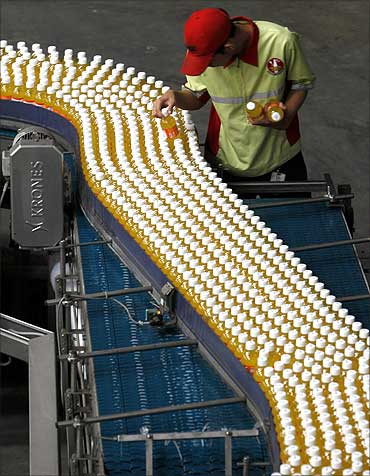 A worker checks drink bottles at PT Coca-Cola Amatil Indonesia's factory in Cibitung.