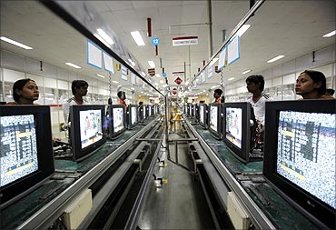 Workers at LG Electronics India Pvt Ltd. assemble television sets inside a factory.