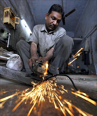A blacksmith works inside an iron workshop on the outskirts of the western Indian city of Ahmedabad.