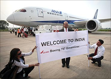 Boeing India President Dinesh Keskar (C) poses in front of the Boeing 787 Dreamliner in Delhi.
