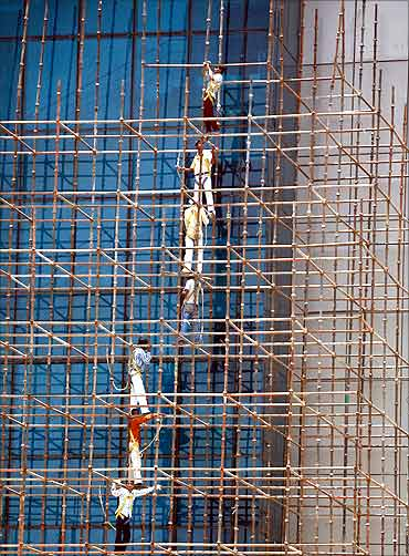 Men work at the construction site of a commercial complex in New Delhi.