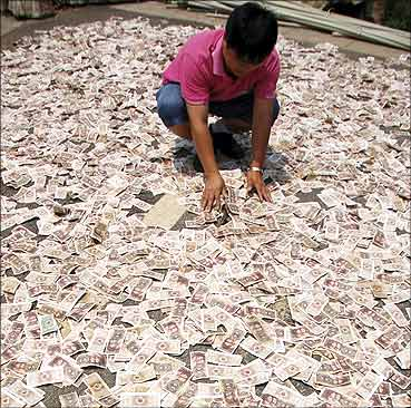 A 35-year-old man spreads one jiao and two jiao banknotes to dry in the sun in Kaili, Guizhou.
