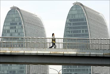 A woman walks on a pedestrian bridge in front of office buildings in Beijing.