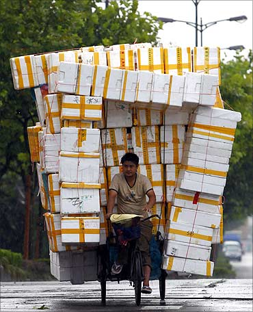 A Chinese man rides his tricycle laden with recyclable styrofoam along a main road in Shanghai.