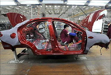 An employee assembles a car at the production line of Anhui Jianghuai Automobile Co in Hefei.