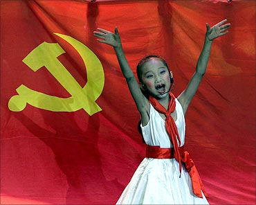 A schoolgirl performs in front of the flag of China's Communist Party during a song concert.