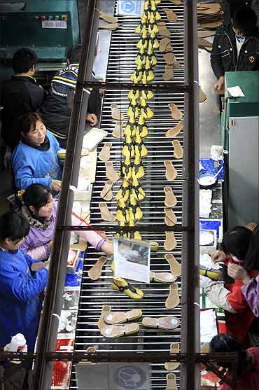 Workers make shoes, to be exported to the US.