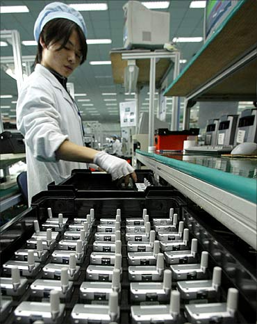 A Chinese worker checks mobile phones at a production line of Ningbo Bird Co.