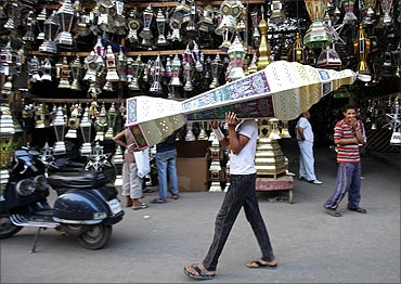 A man carries a traditional lantern called fanous in front of a shop selling lanterns on a street in Cairo.